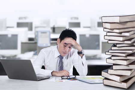 tired businessman: Overworked businessman with laptop and a stack of books in the office