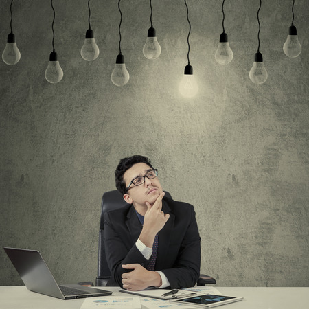 pensamiento creativo: Hombre de negocios caucásico joven, pensando y mirando brillante de la bombilla