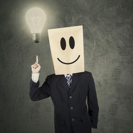 carita feliz: Empresario en traje de negocios con la cabeza de la bolsa de papel que apunta a la bombilla, que simboliza una idea brillante
