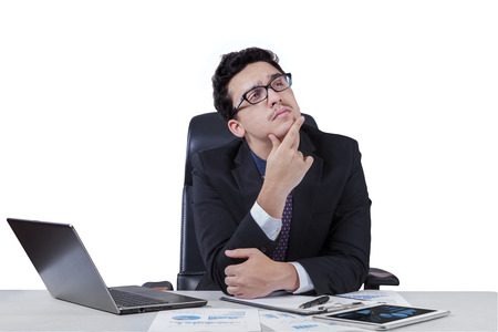 Thoughtful young businessperson in business suit working on desk while thinking a plan, isolated on white photo