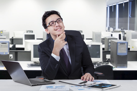 Portrait of young businessman imagine his idea while smiling happy at the workplace photo