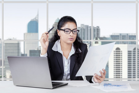 Portrait of young asian woman working in the office while reading a paperwork photo