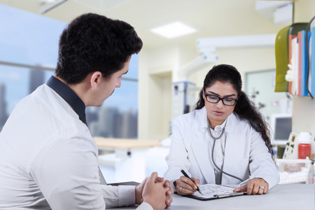 doctor visit: Young female doctor making prescription for her patient on a paper, shot in the hospital Stock Photo