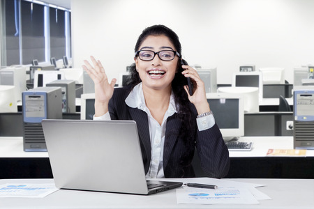 Joyful indian businesswoman listening good news on the phone and smiling happy