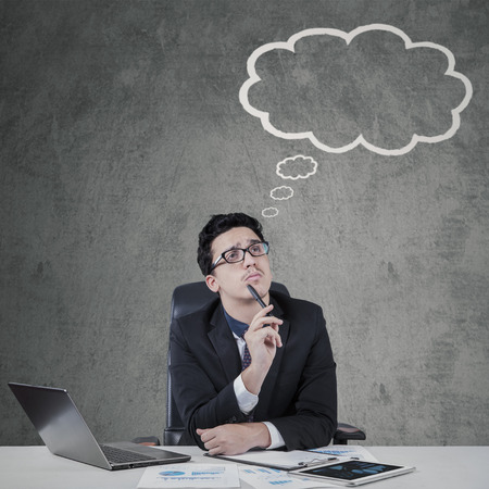 imagines: Thoughtful male entrepreneur looking at a cloud tag while imagines his ideas Stock Photo