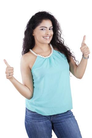 Portret van vriendelijke Indiase vrouw met krullend haar duim opdagen in de studio, geïsoleerd op wit