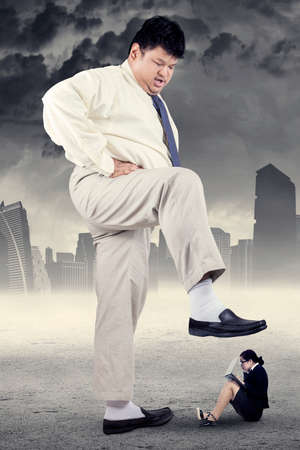 trampled: Business competition concept with little female entrepreneur trampled by big businessman
