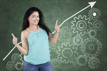 woman engineer: Young indian woman with casual clothes and curly hair showing thumbs up in front of business gear background