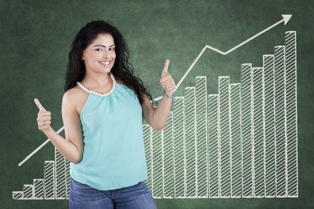 sales manager: Young casual businesswoman standing in front of financial chart and showing thumbs up