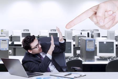 acoso laboral: Hombre de negocios joven que tiene un problema en la oficina y acosado por alguien