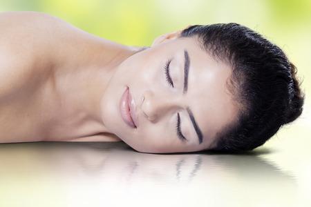fille indienne: Belle jeune mannequin avec une peau fra�che, d�tente dans le studio avec la r�flexion de l'eau Banque d'images