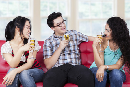 multi ethnic: Multi ethnic people sitting on sofa while drinking champagne and talking each other Stock Photo