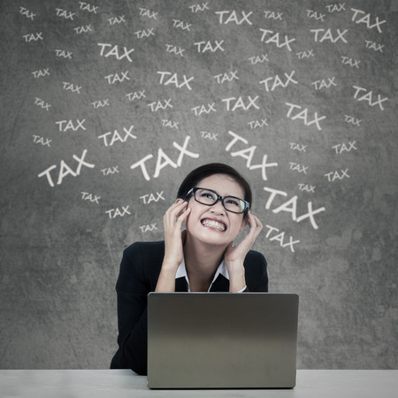 Confused businesswoman with laptop computer having problems to pay her tax photo