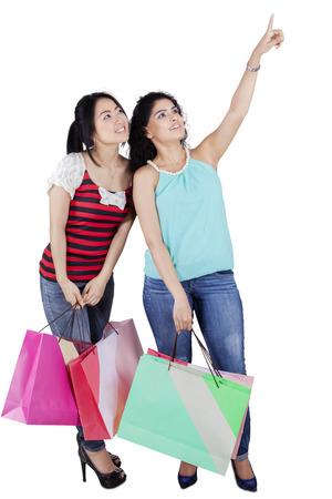fille indienne: Longueur totale de deux fille asiatique debout dans le studio tout en transportant des sacs et en regardant copyspace