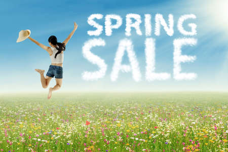 Portrait of happy woman jumping on the meadow with spring sale clouds photo