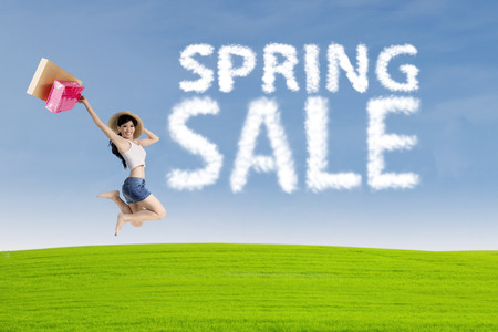 short sale: Happy young woman jumping near cloud of spring sale