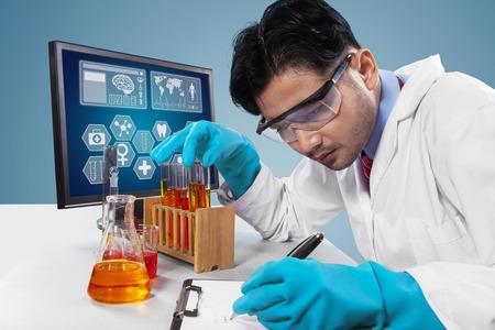 microbiologia: Científico joven que trabaja en el laboratorio, mientras que hace el experimento y escribe el informe en el portapapeles Foto de archivo