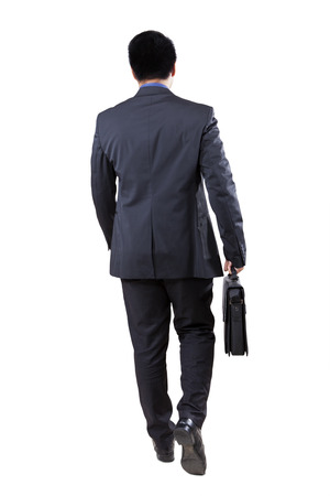Rear view of male businessperson walking in the studio while carrying briefcase photo