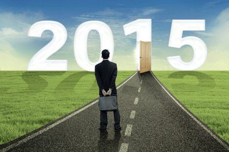 Man standing on the road and looking at the door to his aim in future 2015 photo