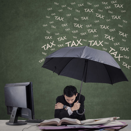 Frustrated businessman using umbrella for protecting him from tax photo