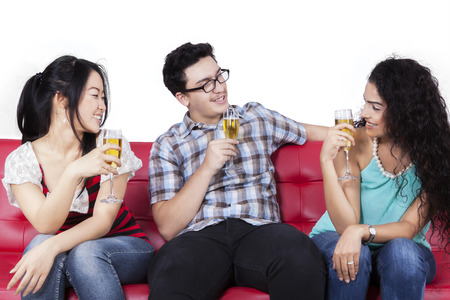 multi ethnic: Joyful multi ethnic people sitting on couch while drinking beer together, isolated on white background Stock Photo