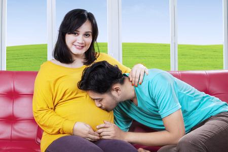 mujer alegre: Marido orgulloso que besa a su esposa embarazada vientre en el sof�, dispar� en casa Foto de archivo