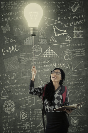 turn on: Attractive college student turn on the light in the class with the blackboard full of the scribble Stock Photo