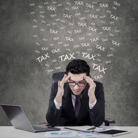 dolor de cabeza: Retrato de joven hombre de negocios cauc�sico tiene dolor de cabeza al contar su impuesto