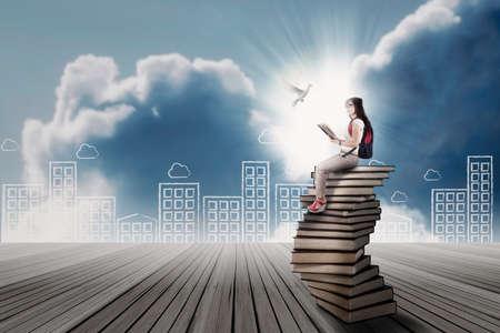 libros volando: Estudiante que se sienta en una pila de libros, mientras que mirando a vuelo de la paloma