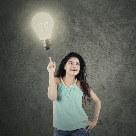 Cheerful woman with a curly hair pointing at a lightbulb symbolizing the creativity photo