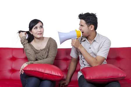 scold: Portrait of young man using a megaphone to scold his wife Stock Photo