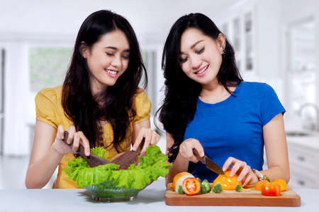 asian cook: Pretty asian women cooking together and make vegetables salad in the kitchen at home