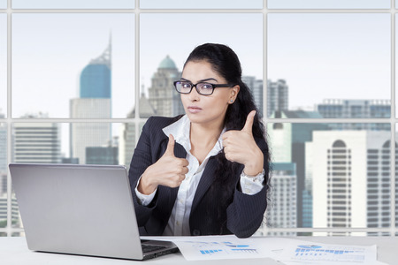Successful indian businesswoman showing thumbs up in the office while working with laptop Stock Photo