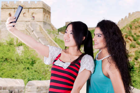 great wall: Two multicultural women using smartphone to take self picture at the Great Wall of China