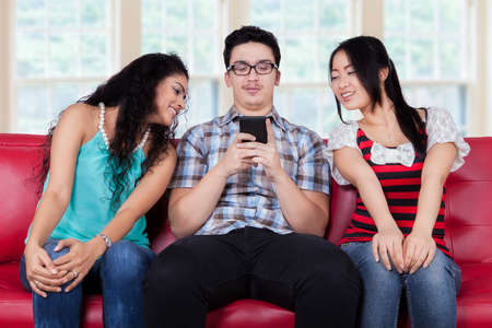 Portrait of caucasian person sitting on sofa with curios girls looking at his smartphone photo