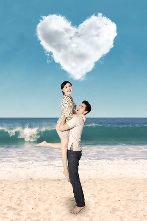 under heart: Attractive asian couple having fun at beach under heart shaped cloud Stock Photo