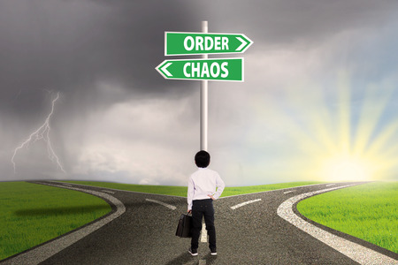 chaos order: Little businessman standing on the road looking at signpost of order and chaos Stock Photo