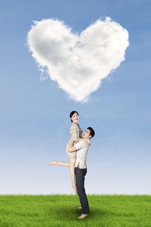 under heart: Full length of couple enjoy holiday and having fun under heart shaped cloud on the meadow Stock Photo