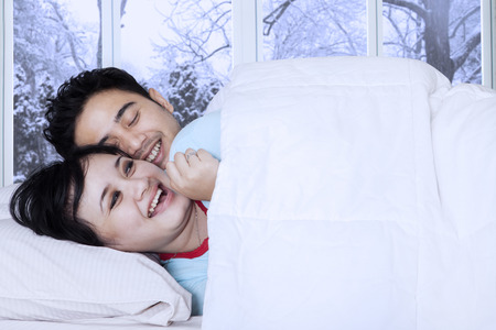 joking: Joyful couple lying on bed and joking together with winter background on the window Stock Photo