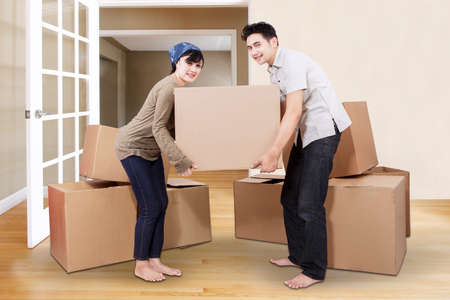 unpacking: Young asian couple unpacking cardboard in new home