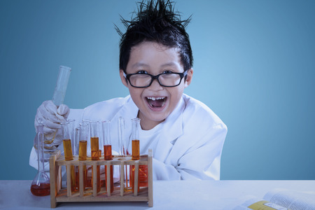 mad scientist: Cute asian boy wearing lab coat doing experiment like a mad scientist
