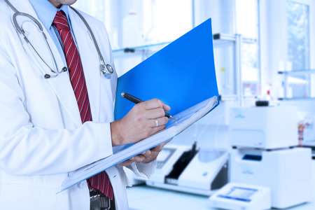 clinical staff: Doctor makes medical record on a folder, shot in the hospital