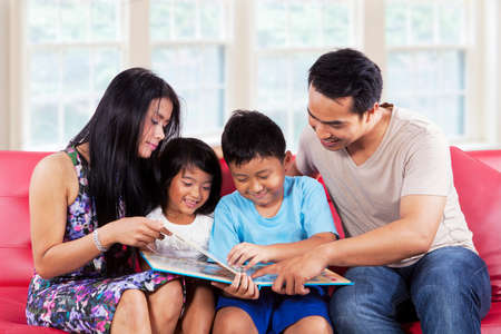 Portrait of hispanic family enjoy read a story book together at home photo