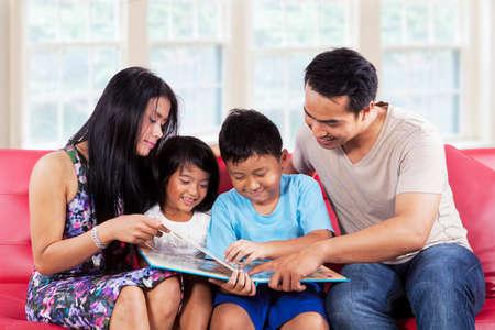 ni�os chinos: Retrato de la familia hisp�nica disfrutar de leer un libro de la historia juntos en casa
