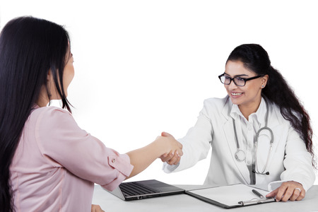 Pretty indian doctor shaking hands to patient while smiling friendly, isolated on white background
