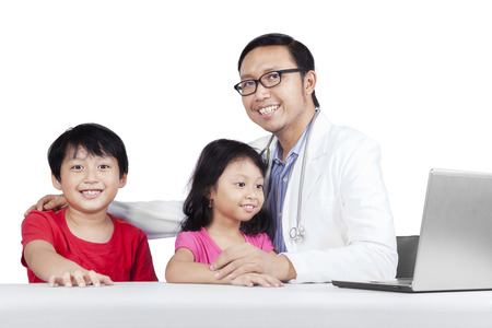 Friendly doctor with children smiling at camera, isolated on white background photo