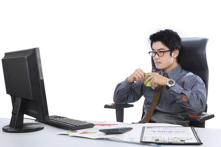 take a break: Young businessman working in the office and take a break while drinking coffee Stock Photo