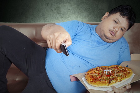 fatty food: Overweight man eats pizza while watching tv at home Stock Photo
