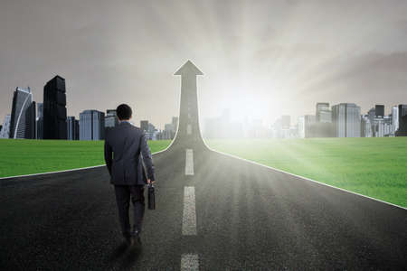 rural development: Businessperson carry a briefcase and walk on the road going up as an arrow Stock Photo