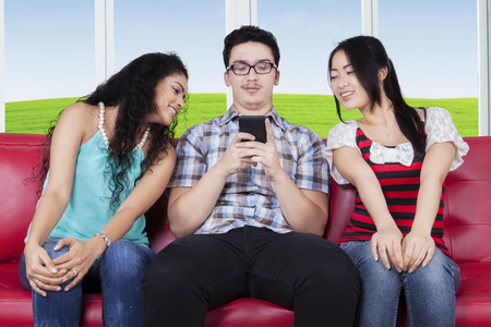 Young caucasian person typing message on the smartphone near curious women photo